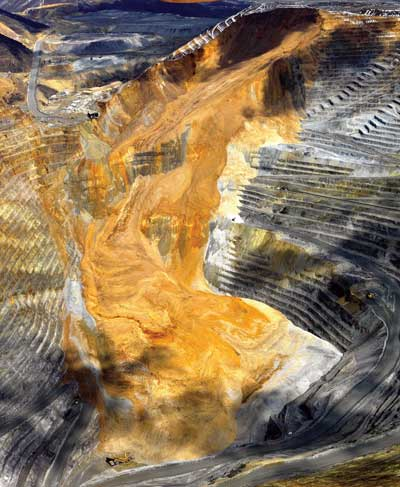 This post-slide photo provided by Kennecott Utah Copper shows how the 2013 Manefay slide damaged infrastructure and changed the size and shape of the century-old Bingham Canyon pit in minutes.