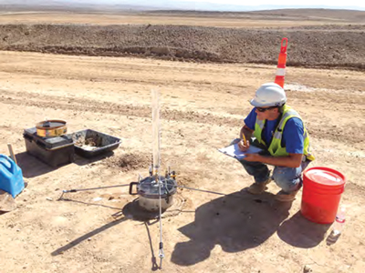 An engineer performs a permeability test on an embankment.
