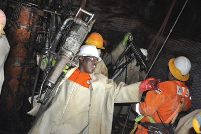 Workers prepare a jumbo before drilling blast holes. The Bakubung mine, a greenfield project, is on schedule to deliver full production by 2020. (Photo by Gavin du Venage)