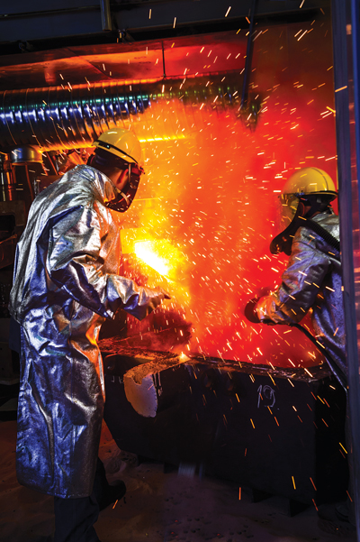 Workers harvest hot metal from a pilot-scale DC furnace at the Outotec Research Center in Pori, Finland.