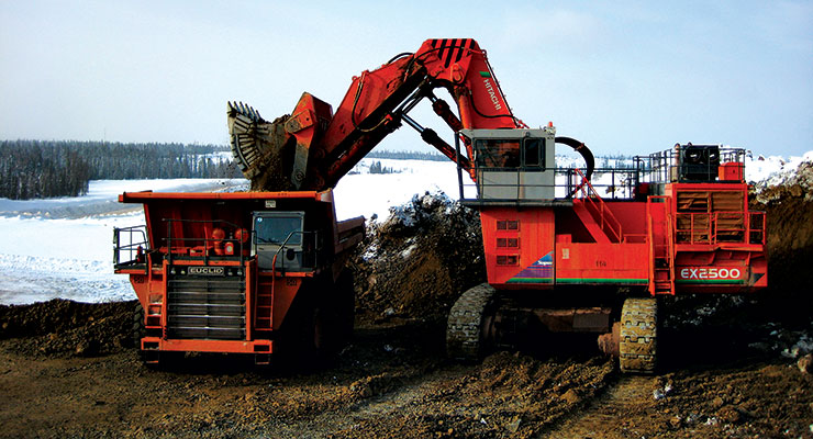 A hydraulic excavator loads bauxite into a haul truck at a North Urals mining operation.