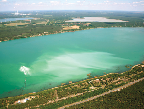 This aerial view shows the pattern of distribution of a lime suspension from a set of nozzles floating just under the water's surface. The initial treatment raised the pH of the lake water from 2.9 to 7.