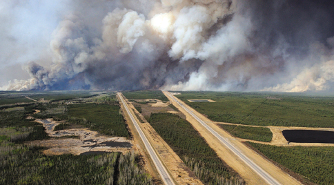 An aerial view of Highway 63 south of Fort McMurray, Alberta, Canada, shows smoke from the wildfires taken from a CH-146 Griffon helicopter on May 5. (Photo: MCPL VanPutten/Canadian Armed Forces/Handout via Reuters)