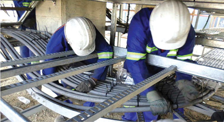 Workers install electrical components during the final stages of construction at Nevsun's zinc concentrator, which was recently completed under budget at an estimated cost of $80 million. (Photo: Nevsun Resources)