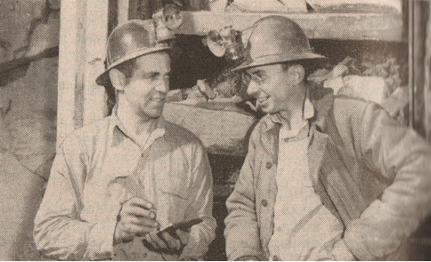Two underground miners talk shop in the 1950s.
